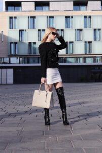 An Gossipgirl angelegtes Outfit, Ich trage eine schwarze Jacke sowie einen weißen Rock.