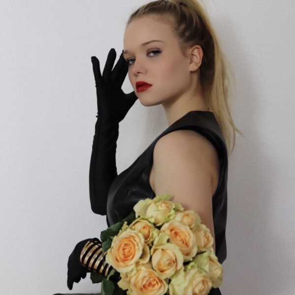Schwarzes Lederkleid mit schwarzen Samthandschuhen und gelben Rosen