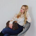 Mädchen mit blonden Haaren sitzt auf einem Stuhl, mit einer blauen Jeans einem Satin Hemd in Cremefarben, auf dem Schoß eine Louis Vuitton Speedy Tasche