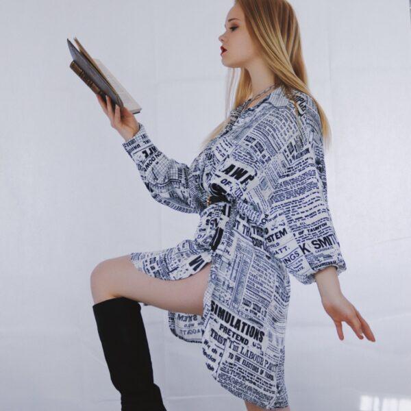 Frau liest Buch und trägt dabei Kniehohe Stiefel und ein Kleid.