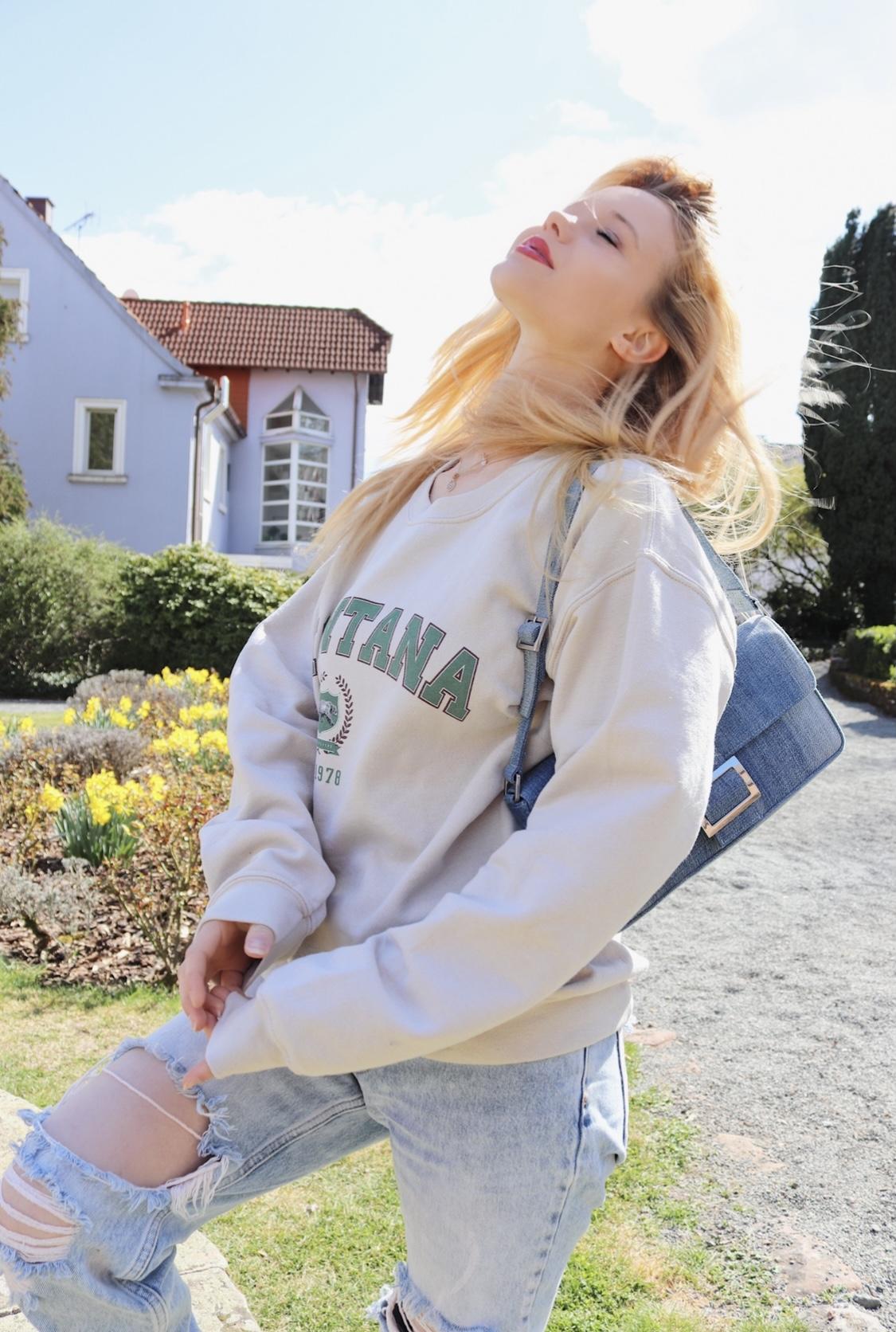 Mädchen. steht in der Frühlingssone, trägt einen Pullover und eine Tasche aus Jeansstoff