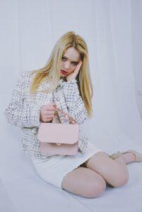 Anne Wendel in einem Outfit bestehend aus einer weißen Tweedjacke, weißem Tweedrock und einer rosafarbenen Tasche v