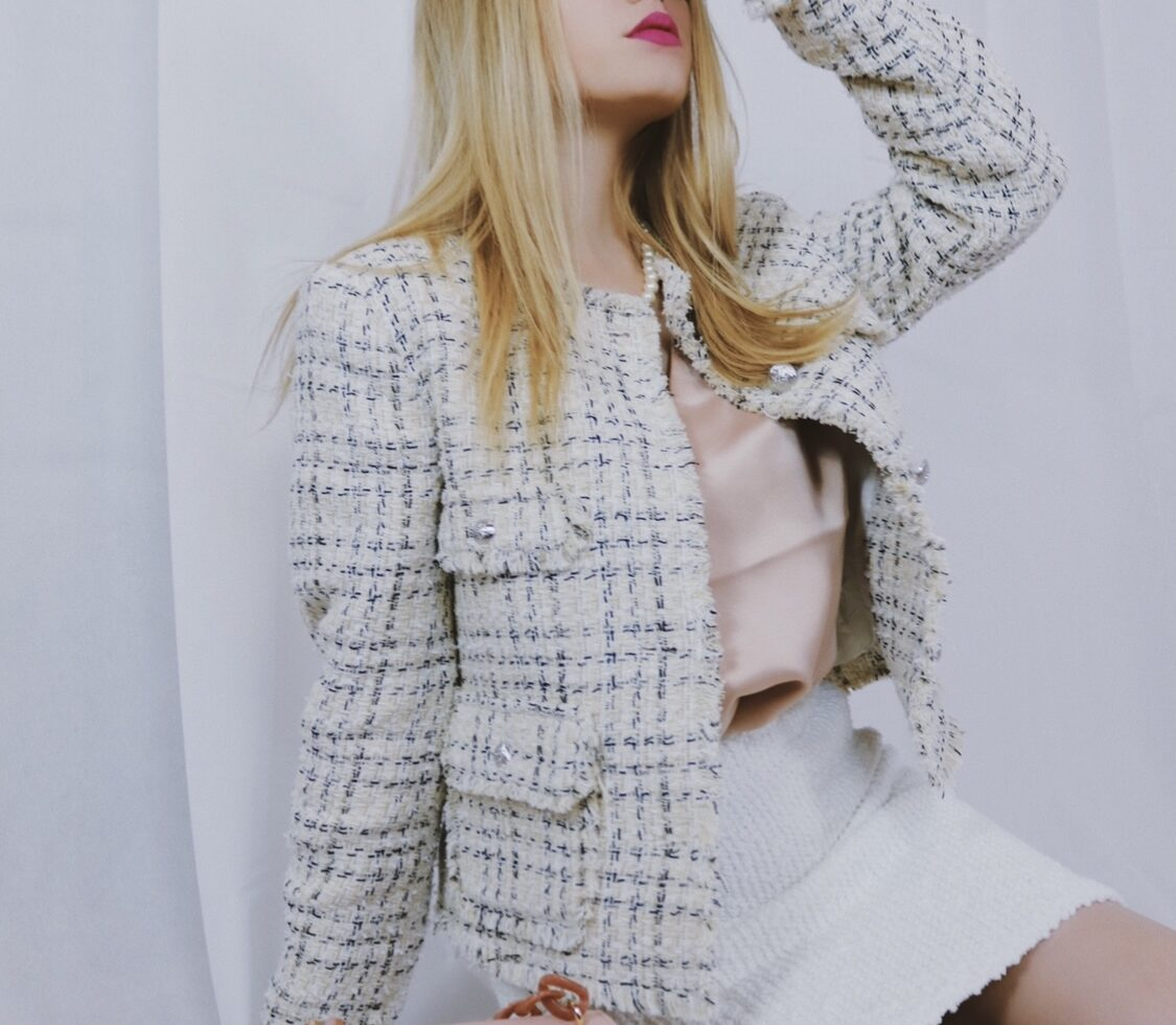 Anne Wendel trägt eine weiße Tweedjacke sowie einen weißen Tweedrock von Mango.